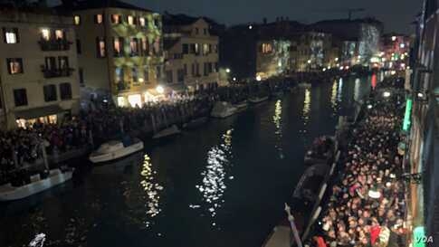 Crowds line up along the canal banks where Venice Carnival floats are expected, in Venice, Italy, Feb. 8, 2020.