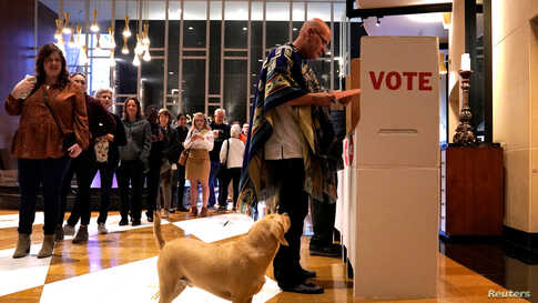 Eddie Craig Monarch reviews his ballot while his dog Sherlock waits at a polling place on Super Tuesday in Oklahoma City