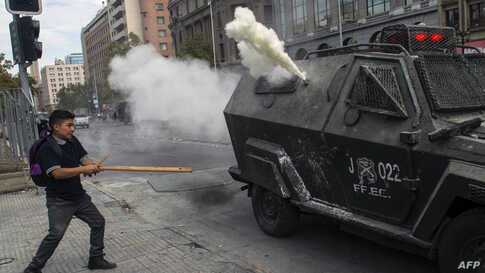 A student confronts riot police during a protest against Chile's President Sebastian Pinera government, in Santiago.
