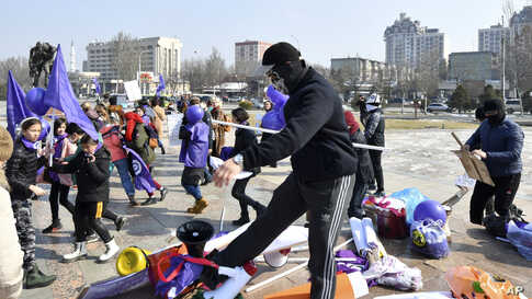 Masked Kyrgyz nationalists attack women's rights activists during the celebration of the International Women's Day at Victory Square in Bishkek, Kyrgyzstan.
