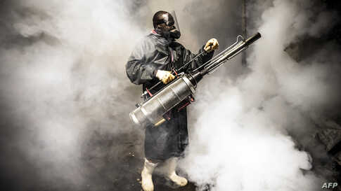 A member of a privately-funded NGO fumigates and disinfects the streets and the stalls at Parklands City Park Market in Kenya to help curb the spread of the coronavirus, April 15, 2020.