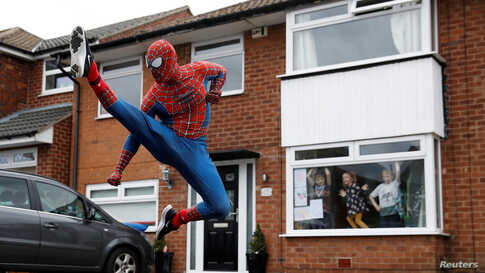 Jason Baird dressed as Spiderman exercise to cheer up local children in Stockport as the spread of the coronavirus disease (COVID-19) continues in Britain.