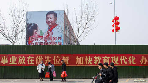 Men ride a scooter past a poster showing Chinese President Xi Jinping on the side of a school building in a newly developed…