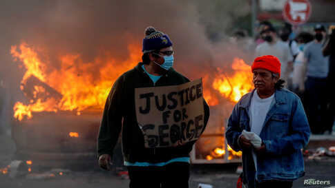 A man wearing a face mask holds a sign near a burning vehicle at the parking lot of a Target store during protests after a…