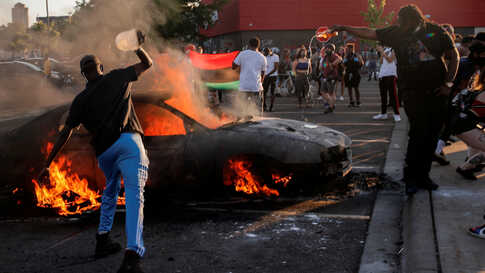 People react as a car burns at the parking lot of a Target store during protests in Minneapolis, Minn.