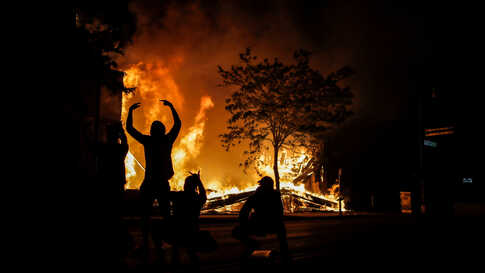 People react as fire rages in the background while protests continue in Minneapolis.