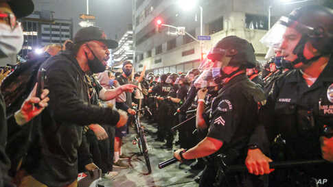 In this May 29, 2020, photo, protesters confront police officers during a protest over the death of George Floyd in Los Angeles…