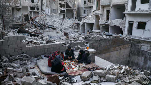 """A displaced family of Tareq Abu Ziad, from the town of Ariha in the southern countryside of the Idlib province, Syria, break their fast for the sunset """"iftar"""" meal, at their destroyed homeduring the Muslim holy month of Ramadan."""