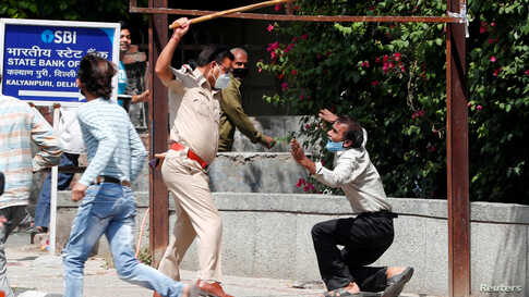 A police officer raises a baton at a man who, according to police, had broken the social distancing rule, outside a wine shop during an extended nationwide lockdown to slow the spread of the coronavirus disease (COVID-19), in New Delhi, India.