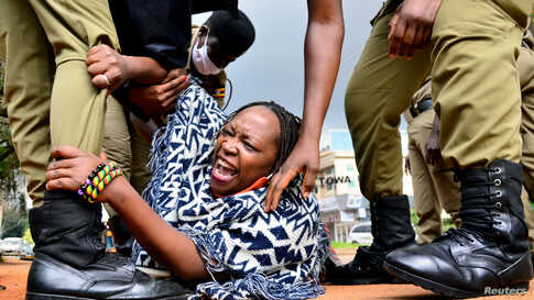 Ugandan academic Stella Nyanzi reacts as police officers detain her for protesting against the way the government distributes the relief food and the lockdown situation to control the spread of the coronavirus disease (COVID-19) outbreak in Kampala.