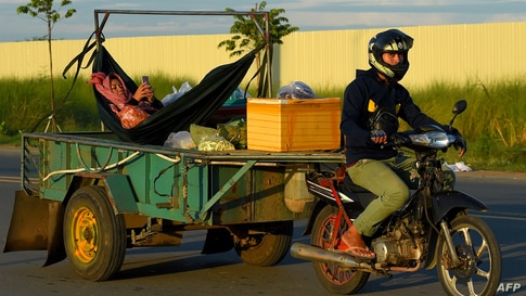 A man rides a motorbike pulling a trailer with a woman relaxing in a hammock, checking her phone, on a street in Phnom Penh on…