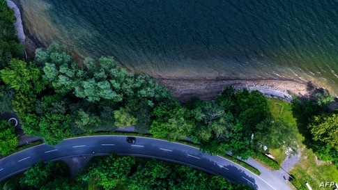 An aerial view taken on June 12, 2020 shows a car driving on a street leading along the banks of the Moehnesee lake in…