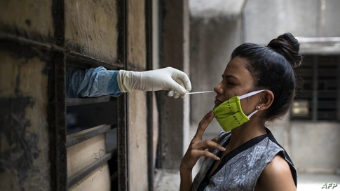 A health official (L) collects a swab sample from a woman to test for the COVID-19 coronavirus at a temporary free testing…