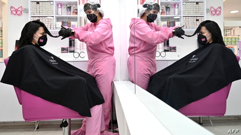 A stylist and a customer wear protective equipment as a preventive measure against the COVID-19 coronavirus, at a beauty salon…