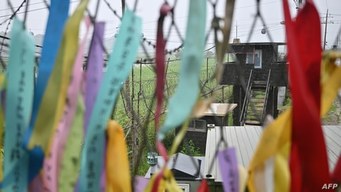 A South Korean guard post is seen through a military fence decorated with ribbons wishing for peace and reunification of the…