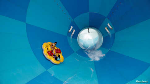 People enjoy a water slide in Yongin, South Korea, as measures to avoid the spread of the coronavirus disease (COVID-19)…