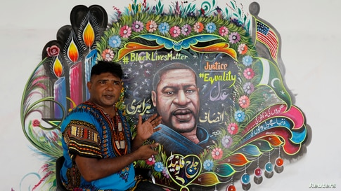 Pakistani truck-art painter Haider Ali, 40, gestures as he speaks with Reuters next to a mural he painted, depicting George…