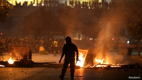 A member of the Lebanese riot police walks near burning fire during a protest against the fall in pound currency and mounting…
