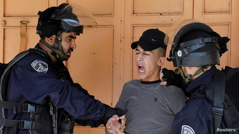 Israeli border police members detain a Palestinian during a protest against Israel's plan to annex parts of the occupied West…
