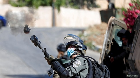 An Israeli border police member fires a tear gas canister towards Palestinians protesting against the demolition of a house…