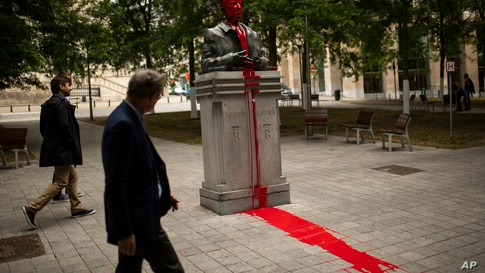 People walk past a bust of former Belgium's King Baudouin being vandalised and covered in red paint in Brussels, Friday, June…