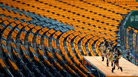 Cheer leaders perform to empty stands prior an opening baseball game between the Yomiuri Giants and the Hanshin Tigers at Tokyo…