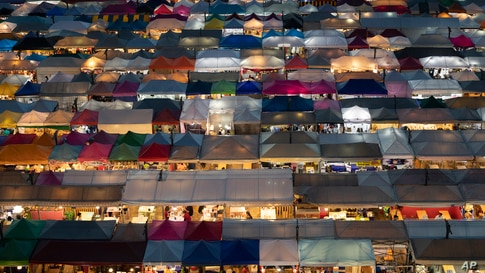 Tents of food stalls and other vendors are illuminated at Rot Fai Market in Bangkok, Thailand, Friday, June 19, 2020. Daily…