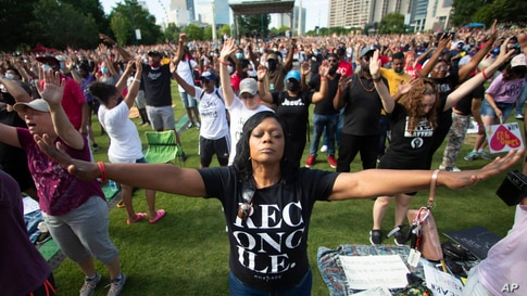 ADDS DESCRIPTION OF ONERACE MOVEMENT - A woman prays during an event hosted by OneRace Movement at Atlanta's Centennial Olympic…