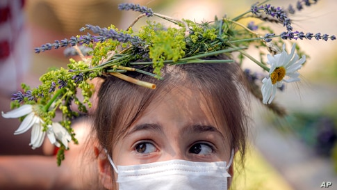 A girl wearing and a face mask to combat the spread of the COVID-19 infections and a flower crown she made herself at a…