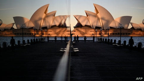 Sunset hues fall on the landmark Sydney Opera House as it is seen in a reflection from Circular Quay, usually packed with tourists, in Sydney, Australia.