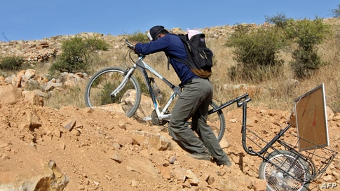 Bolivian teacher Wilfredo Negrete Jaldin pushes his bike carrying a board on his way to his students' homes in Aiquile.