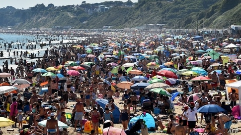 Beachgoers enjoy the sunshine as they sunbathe and play in the sea on Bournemouth beach in Bournemouth, southern England.