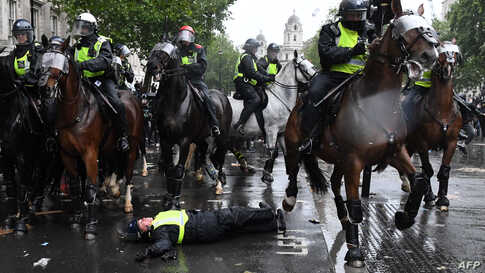 A mounted police officer is seen on the ground after falling from his horse, during a demonstration on Whitehall, near the entrance to Downing Street in central London, June 6, 2020, to show solidarity with the Black Lives Matter movement.