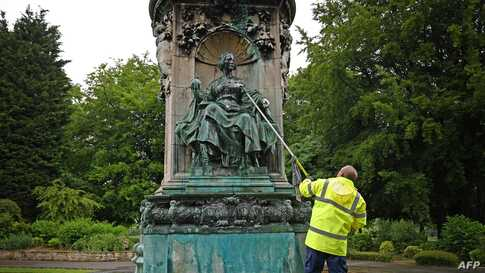 Council workers clean a statue of Britain's Queen Victoria that was defaced in Woodhouse Moor Park in Leeds, northern England.