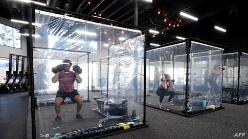 People exercisein their workout pods while observing social distancing at Inspire South Bay Fitness, June 15, 2020, in Redondo Beach, as the gym reopens under California's coronavirus Phase 3 reopening guidelines.