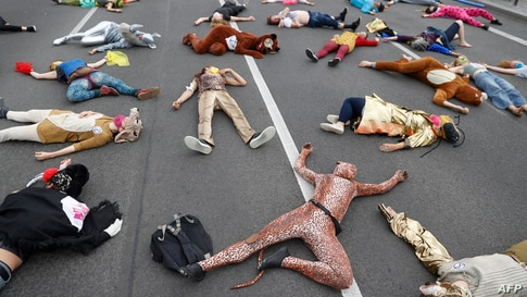 Activists from the Extinction Rebellion movement stage a Die-In as they demonstrate for climate justice in a street in Berlin's Neukoelln district, Germany.