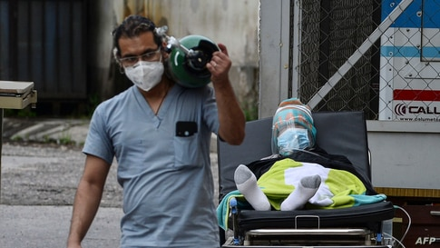 A doctor carries an oxygen tank after disconnecting a man infected with COVID-19 from it at a field hospital set up in the yard of the School Hospital in Tegucigalpa, June 17, 2020.