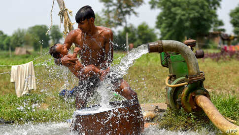 A man gives bath to his son with a water tube well near a field as the temperature rises in New Delhi, India.