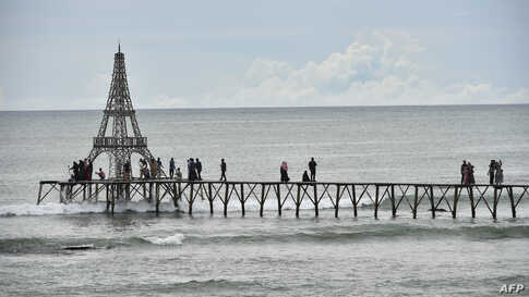 People walk on a pier on Lhokseudu beach, a local tourist attraction in Aceh province, Indonesia.