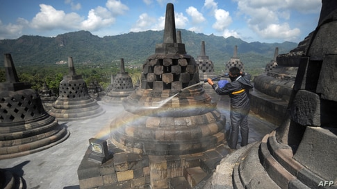 A worker cleans volcanic ash off the stupas at the Borobudur temple in Magelang Regency a day after Mount Merapi erupted in nearby Sleman, sending a plume of ash into the sky.