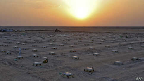 The sun sets over a cemetery for COVID-19 victims, 20 km from the central Iraqi holy city of Najaf, June 10, 2020.