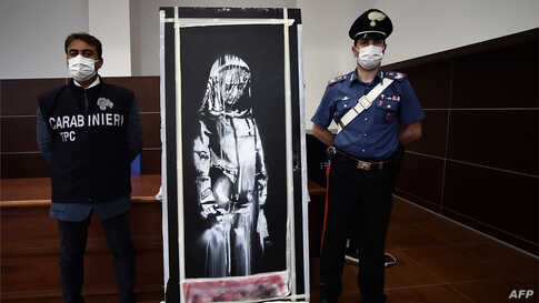 Italian Carabinieri pose near a piece of art attributed to Banksy, that was stolen at the Bataclan in Paris in 2019, and found in Italy, during a press conference in L'Aquila.