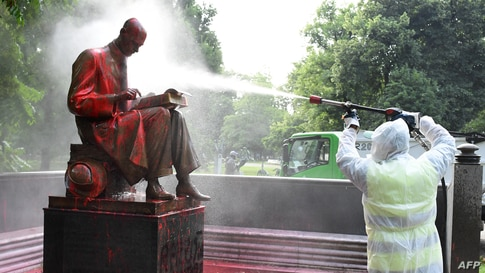 """A municipal employee cleans a statue of a famous Italian journalist Indro Montanelli in a Milan public square, a day after it was defaced, stained with red paint and tagged with the inscription """"racist, rapist."""""""