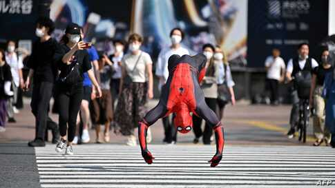 A man wearing a Spiderman costume jumps across Shibuya crossing in Tokyo, Japan.