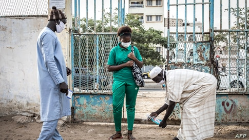 A High School student at the Lycee Blaise Diagne gets her feet disinfected as she arrives for her first day back at school in Dakar, Senegal.
