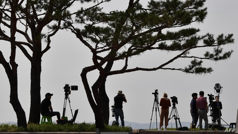 Cameramen record video footage of the North Korean border county of Kaepoong from a South Korean observation post in the border city of Paju.