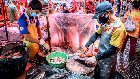Vendors clean fish at Khlong Toei Market, the biggest fresh market in Bangkok, Thailand.