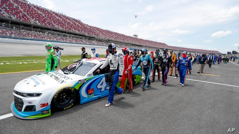 NASCAR drivers and crews push the car of Bubba Wallace to the front of the field prior to the start of the NASCAR Cup Series auto race at the Talladega Superspeedway in Talladega, Alabama, June 22, 2020.