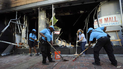 Workers and a volunteer clean up damage outside a burned-out clothing store in Birmingham, Alabama, June 1, 2020, following a night of unrest.