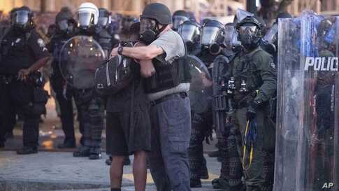 A police officer embraces a protester who helped disperse a crowd of people during a demonstration, June 1, 2020, in Atlanta, Georgia, over the death of George Floyd, who died after being restrained by Minneapolis police officers on May 25.